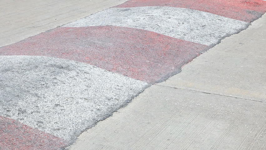 Red and white stripe speed bump on a road when cars is passing