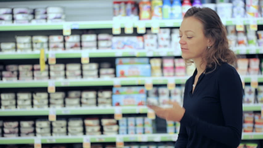 Young woman shopping in the yogurt section at the grocery store. | Shutterstock HD Video #17725933
