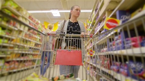 Caucasian woman walking along wholesale shelves and taking goods in shop trolley, beautiful young wife shopping in a supermarket