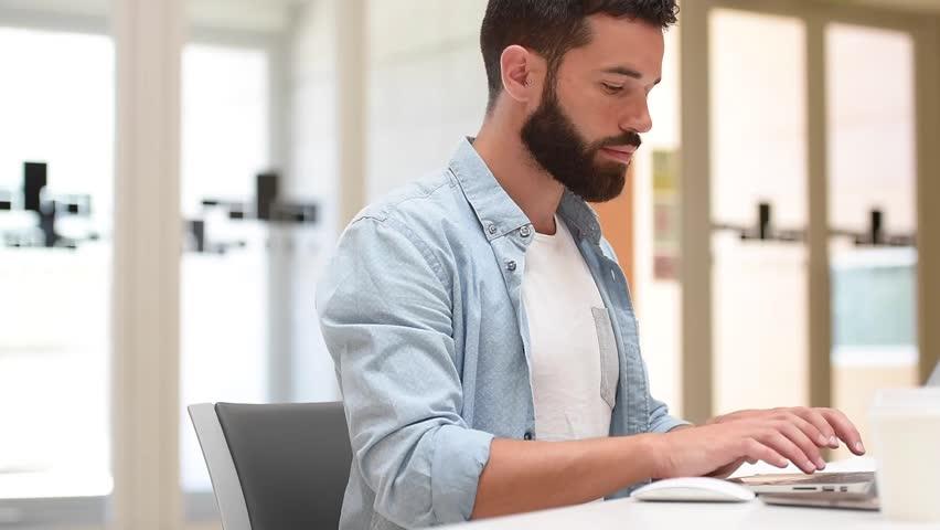 Trendy bearded guy in office working on laptop | Shutterstock HD Video #17759614