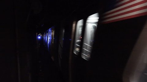 Loop of subway moving through dark tunnel. Loopable inside subway tunnel with blue traffic signal light. Blurry train moves through underground railway in restricted area for people.