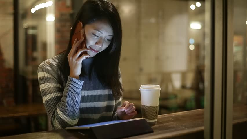 Woman talk to mobile phone and use of digital tablet computer at night