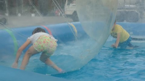 Little boy and girl playing in a transparent bubble floating in water. Slow motion.