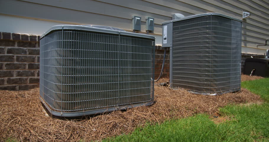 Two Air Conditioning Units on Side of Home Rising Shot. camera rises on two central air conditioning units on the side of a home. Camera tilts down to show the top of the units
