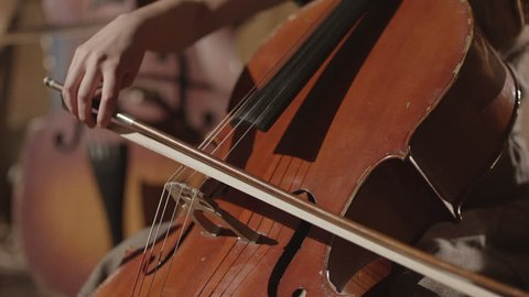 Young musician girl playing with cello violoncello in symphonic hall. Shot on RED EPIC Cinema Camera in slow motion.