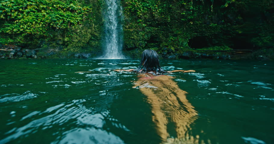 Young woman swimming under jungle waterfall