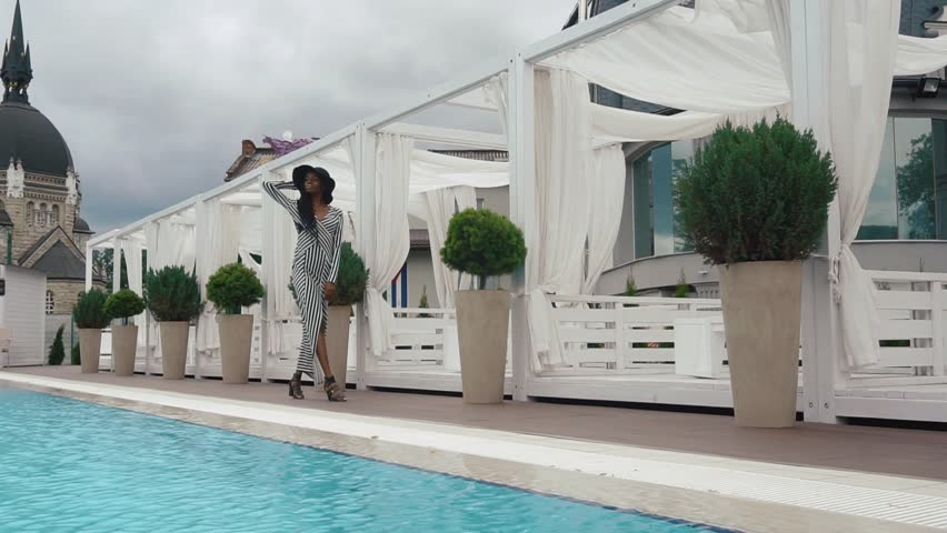 Slow-motion. Sexy elegant african american female model in cocktail striped dress and black hat walks at the luxury pool in hotel as on podium. Vogue concept