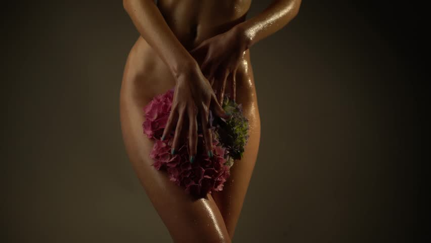erotic naked wet woman stroking beautiful flowers between her sexy legs