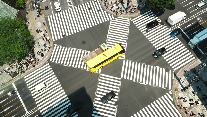 Tokyo - Aerial view of junction with traffic and people on crosswalk. 4K resolution time lapse spinning zoom in. Ginza. May 2016