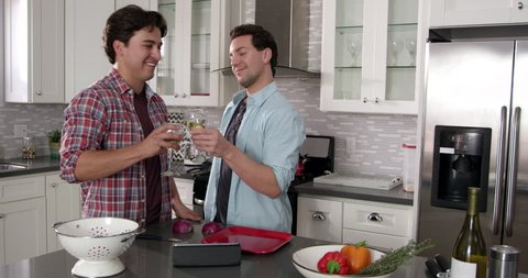 Male gay couple preparing a meal and drinking wine, shot on R3D