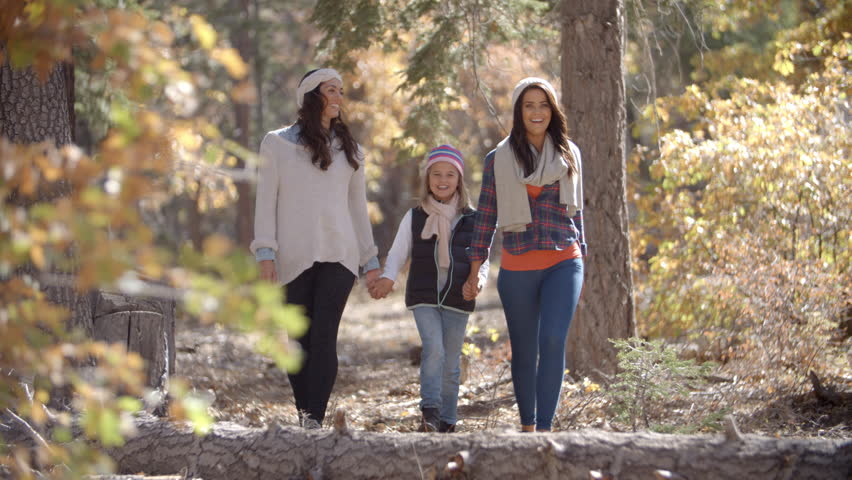 Female parents walk in a forest holding hands with daughter