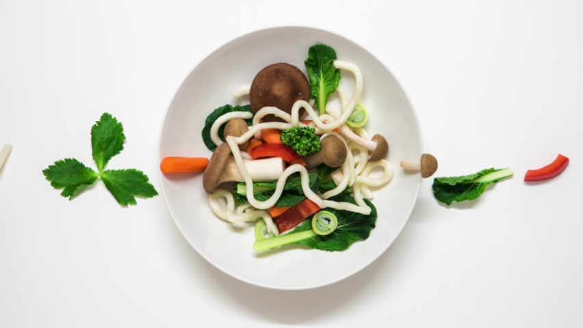 Vegetables and udon noodles becoming a soup. Fresh ingredients entering the plate and than they are cooked. Stop motion animation on white background. 4K resolution