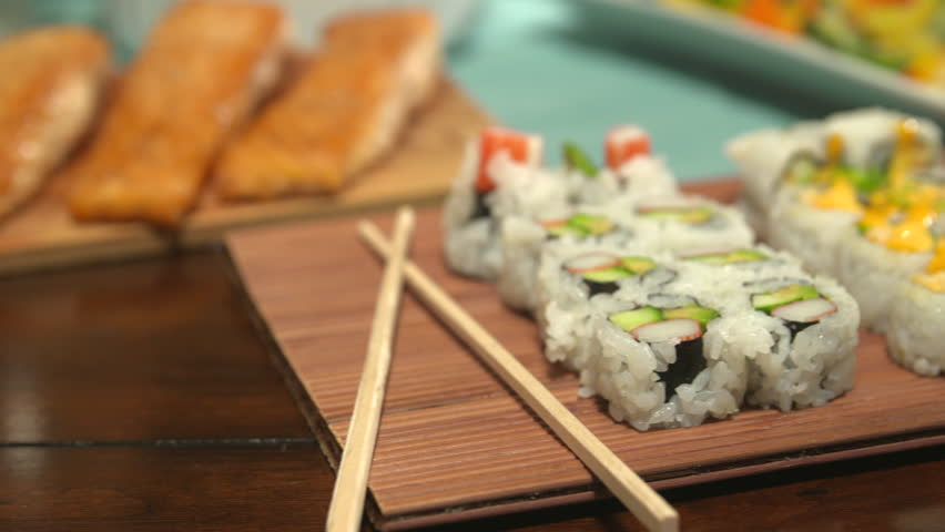 Sushi Close Up Move Right on a Table Spread. camera moves right over a variety of sushi with chop sticks, surrounded by a variety of other foods for a party    Shutterstock HD Video #17950264