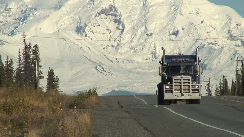 Truck Drives In Front Of Snow Covered Mountain