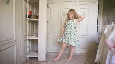 Happy blonde girl in the dress having fun dancing indoors in a sunny white room at home or kindergarten
