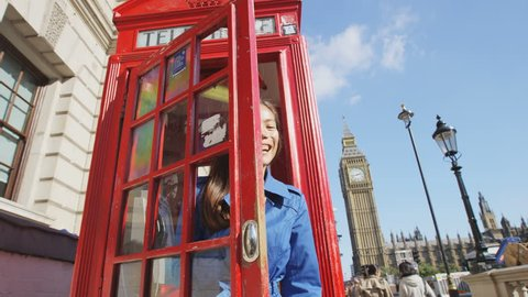 Cheerful woman waving while coming out of phone booth. Young female is enjoying her vacation in London. by Big Ben famous tourist attraction destination landmark. England, UK. SLOW MOTION RED EPIC.
