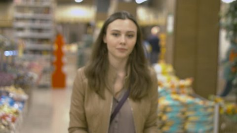Sweet young woman walking on the supermarket