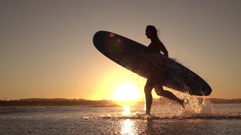 SLOW MOTION SILHOUETTE: Young surfer girl enjoying seaside summer vacation activities, holding longboard surfboard and running in shallow water in beautiful ocean at amazing golden light sunset