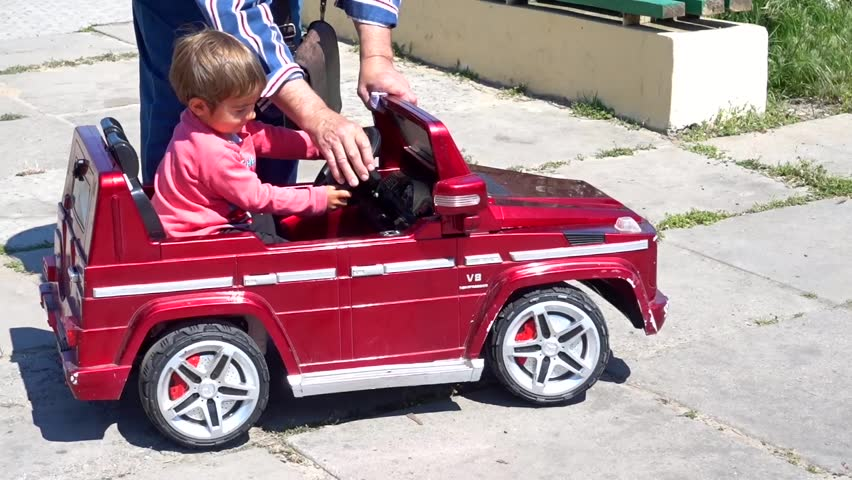 Child learns how to drive a ride on car by himself pushing accelerator pedal, his granddad helps