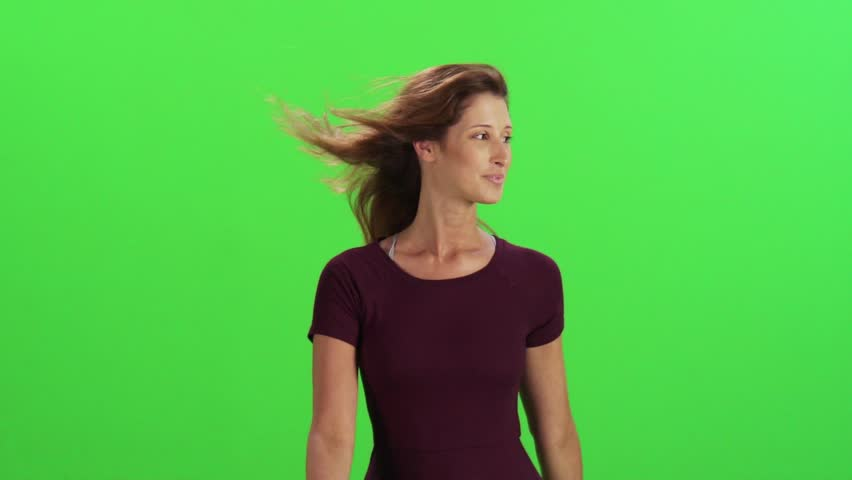 Young woman walking in a medium frontal shot, looking around and smiling, slow-motion (100 fps)