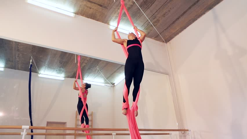 Sport. Beautiful dancer on aerial silk in studio. Air acrobatic young women takes the twine. Female gymnast in black concert suit performing on pink aerial silk in the rehearsal hall. | Shutterstock HD Video #18058834