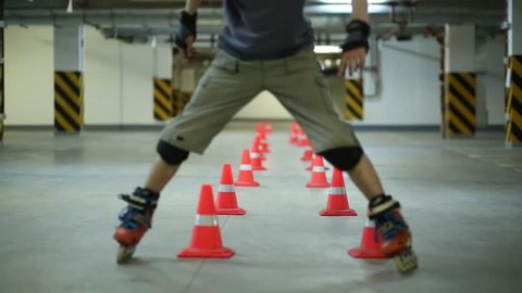 Man slowly circling lines of cones pushing legs backwards on roller skates on parking.