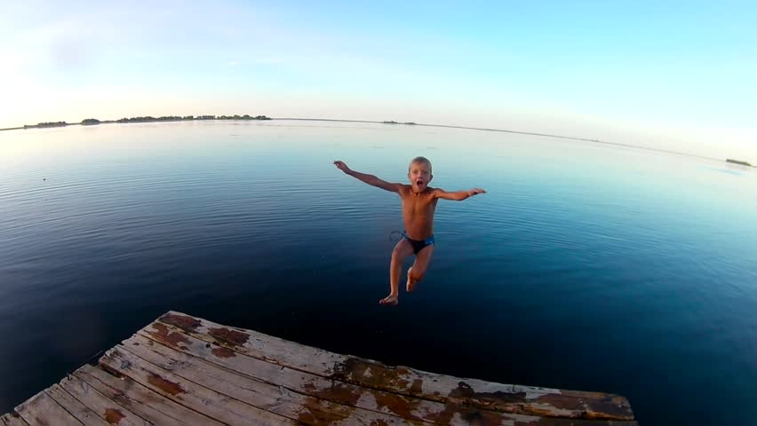 Kid jumps off a wooden dock into the water . Slow motion