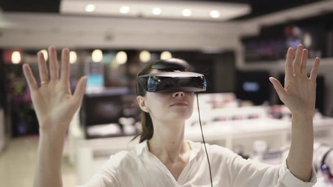 Young woman getting experience in using vr-headset in a mall
