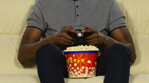 Man holding a joystick and eating popcorn