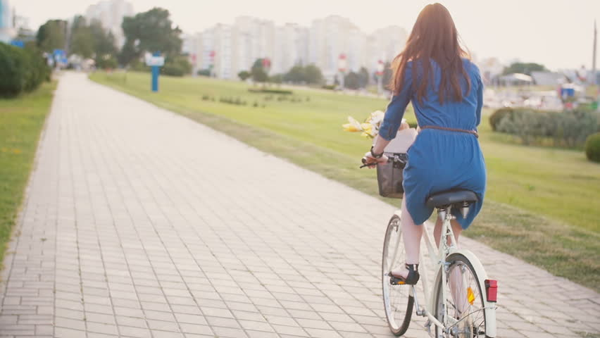Side view of a girl cycling on a road with flowers in a basket and exploring the city, slow mo, steadicam shot