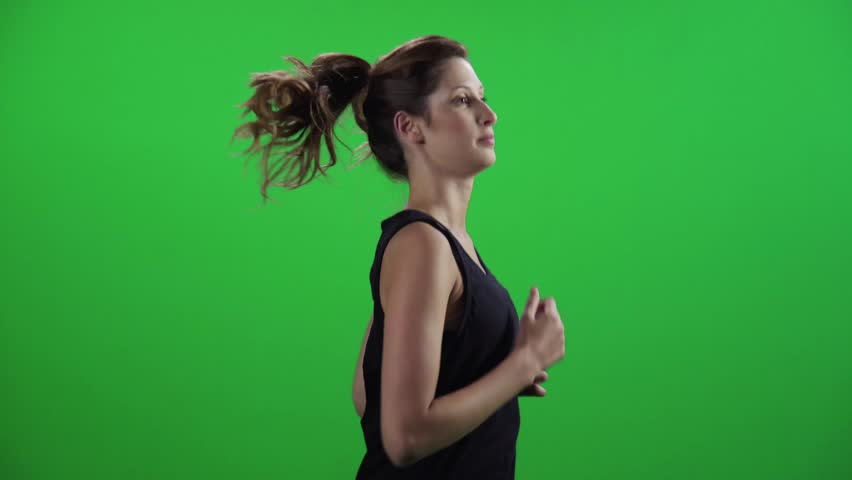 Young woman jogging in a medium frontal shot over a green screen, smiles.