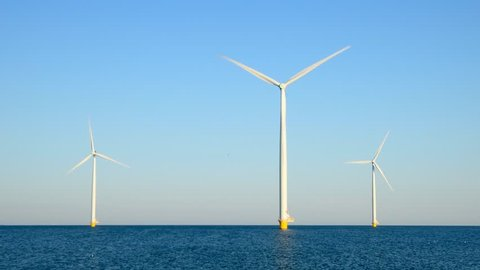 Wind turbines with rotating blades in an offshore wind park during a beautiful summer day. Loop ready cinemagraph clip