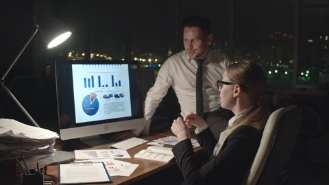 Medium shot of business man and woman analyzing financial statistical data on computer screen in dark office at night, medium shot on Sony NEX700 + Odyssey 7Q