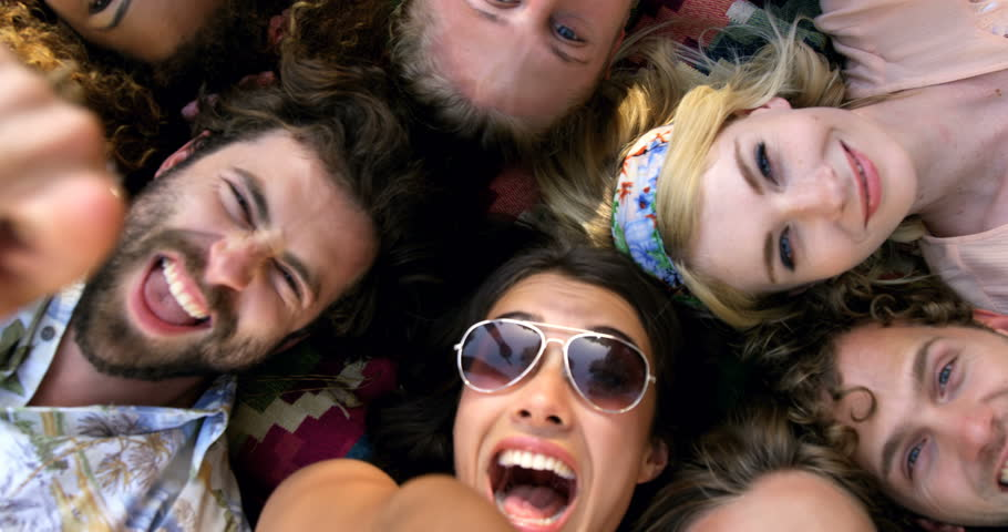 Hipsters friends lying and pointing the camera in a festival