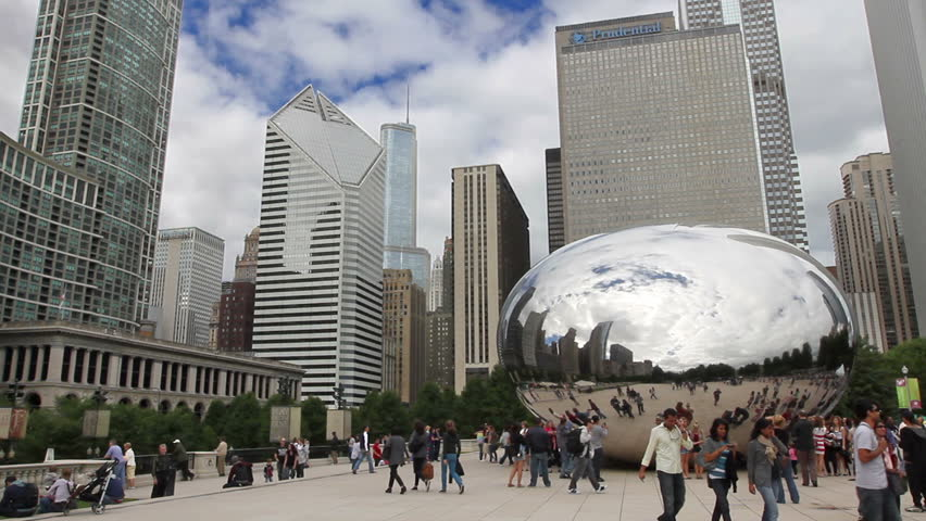 CHICAGO - CIRCA SEPTEMBER 5, 2011 - Tourists admire the Cloud Gate sculpture in Millennium Park, with skyscrapers in the background