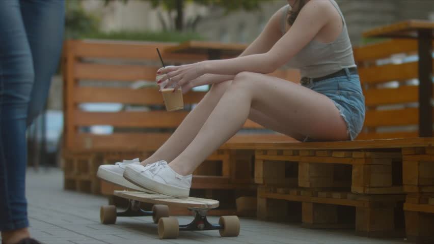 Close up shot of legs of young Caucasian hipster girl sitting on the stairs with a longboard skateboard and drinking milkshake. 60 FPS 4K UHD