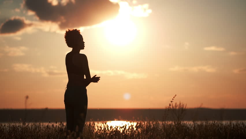 Silhouette of young beautiful girl practicing yoga at sunset. Slow motion. | Shutterstock HD Video #18196282