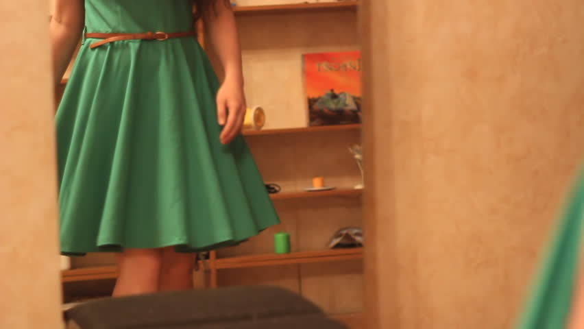 Beautiful girl with long hair spinning beside a mirror in a green dress slow motion. Attractive woman trying on clothes.