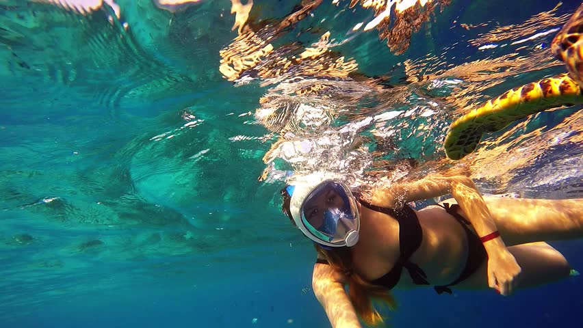 Young sexy woman selfie with sea turtle in Maldives
