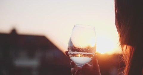 Woman Drinking Cooled White Wine from a glass at the Balcony during Sunset. Slow Motion 120 fps, 4K DCi. Beautiful female enjoying cozy evening on terrace. Summertime relax at sunny patio. Lens Flare
