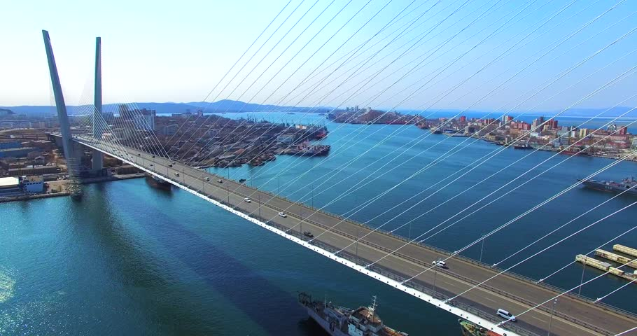 Great zooming in aerial view of the Zolotoy Bridge (the Golden Bridge) that is cable-stayed bridge across the Zolotoy Rog built in 2012 in Vladivostok, Russia, and cars driving on it.