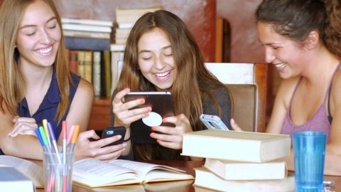 A group of attractive teenage girls laughing and having a good time with their smart phones, tablets and technology.