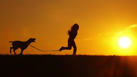 Pretty young girl running with her dog outdoors on sunset backlit by sun, slow motion.