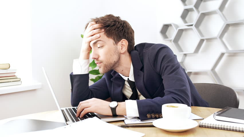 Young successful businessman working at laptop, falling asleep in office. Slow motion.