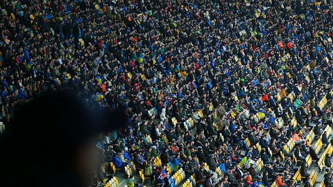 Millions of football fans sitting on tribunes and watching match, sporting event