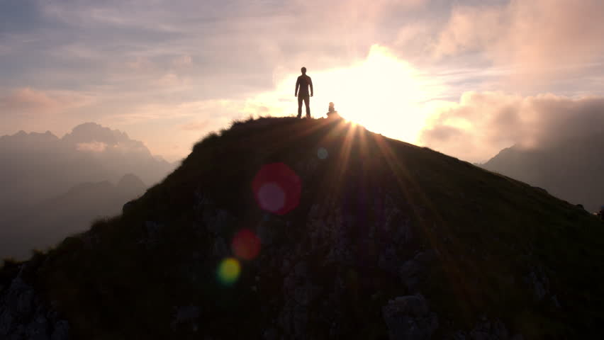 Aerial - Moving above silhouette of a man standing on top of the mountain. Man raising arms victoriously after climbing the mountain