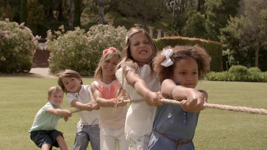 Five children pulling rope having tug of war in park