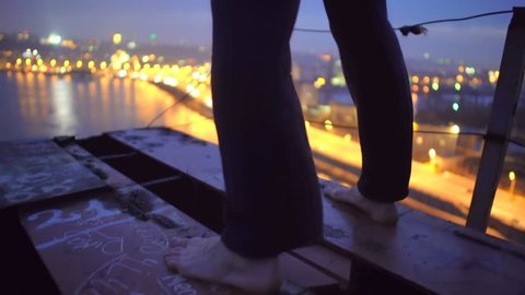 Barefoot man standing on bridge edge, thinking about suicide, changing his mind