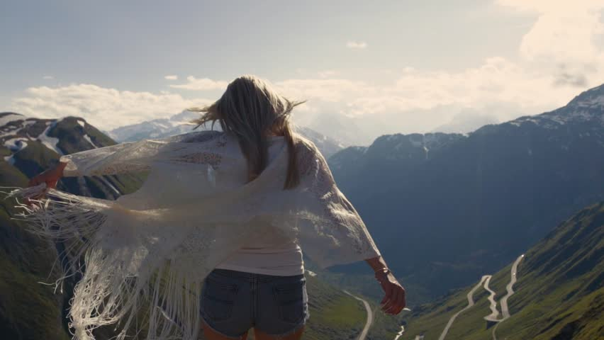 Charming girl is on top of the world, playing with the wind, great mountains on the background. Slow motion and shots stabilizer. Amazing snowy Alps