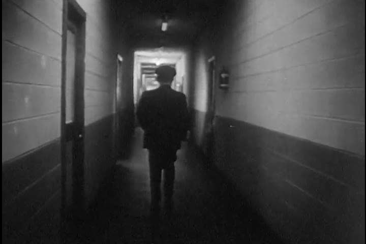 A security guard walks the hallway with his flashlight at a Zenith facility in the 1950s. (1950s)   Shutterstock HD Video #18464194